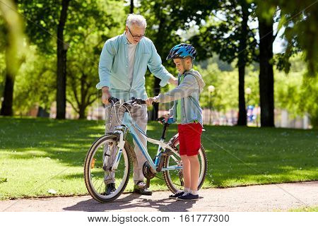 family, generation, safety and people concept - happy grandfather teaching boy with bicycle and bike helmet at summer park