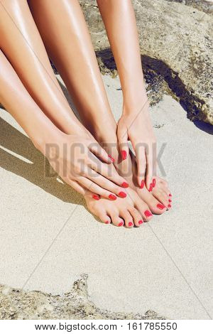 Pretty woman feet and hands with red pedicure and manicure: relaxing on sand. Holiday, vacation, spa, summer: concept.
