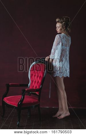 shy and Young beautiful bride in elegant white robe standing near the chair in a marsala interior.