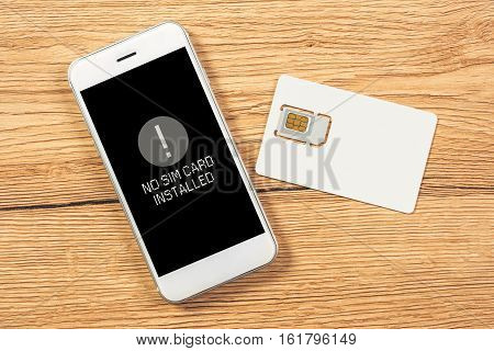 No SIM card installed notification on smartphone screen top view mock up for telecommunication provider microchip with mobile phone on office desktop