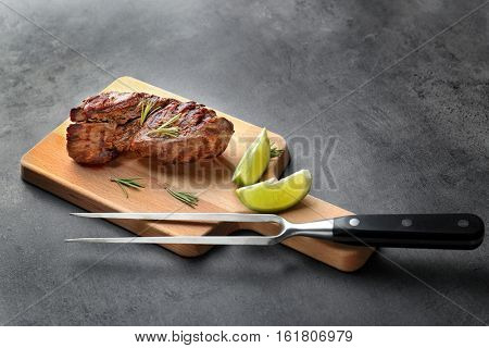 Composition of tasty steak, rosemary and lime on kitchen table