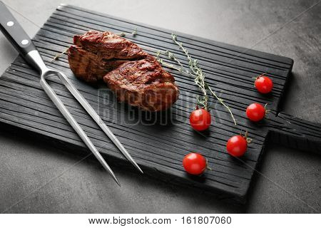 Composition of tasty steak, thyme and cherry tomatoes on kitchen board