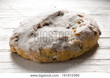 Single whole christmas stollen on white wooden background