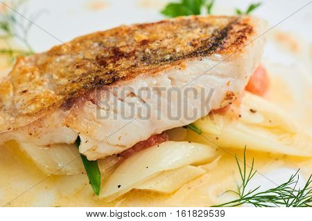 Pike perch fillet with leeks and beurre Blanc served in a white plate