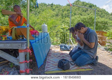 Kanchanaburi, Thailand - August 21, 2016: A monk sprinkled holy water to tourists. AT Wat Ban Tham Temple, Kanchanaburi Province, Thailand, Religion, Buddhism