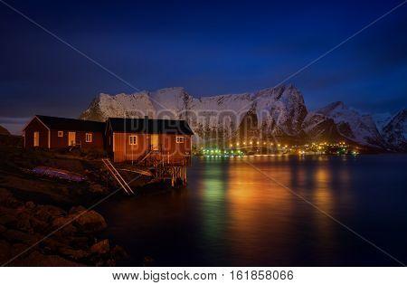 Rorbu in Reine at night with mountains and illuminated bridge in background Lofoten