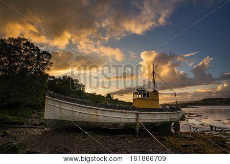 Old boat in old harbour nera Kyleakin in sunset light Isle of Skye Scotland