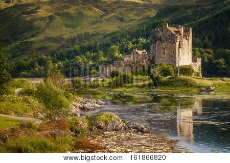 Eilean Donan Castle with reflections in water in sunny day Highlands Scotland