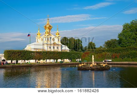 PETERHOF, SAINT - PETERSBURG, RUSSIA - AUGUST 19, 2016: The Upper Garden. The Eastern Square Pond Fountain and Apollo Sculpture. On the background is The Grand Palace Church of Saints Peter and Paul