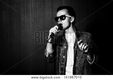 Young Guy in Sunglasses and Jeans Jacket Singing with Microphone. Singer Performance. Concert and Music Concept. Dark Background. Black and White Photo.