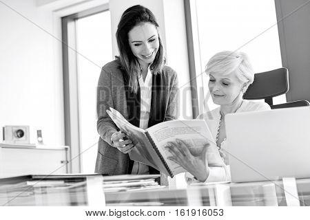 Smiling businesswomen reading book at desk in office