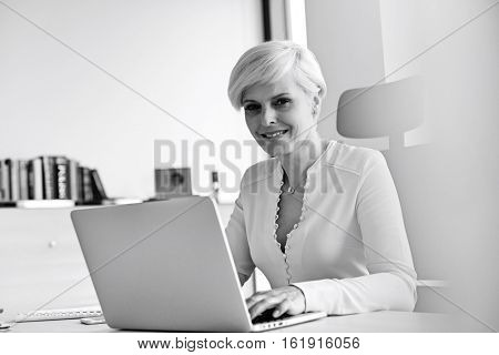 Portrait of smiling mature businesswoman using laptop at desk in office