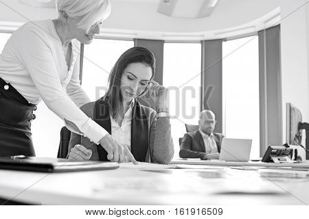 Businesswomen discussing over project with male colleague in background at office