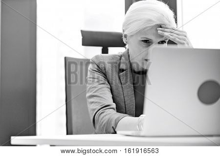 Tired mature businesswoman using laptop at desk in office