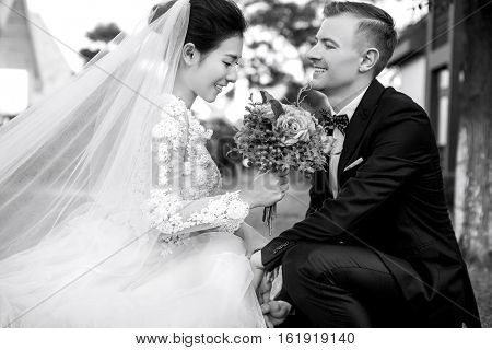 Happy bridegroom looking at beautiful bride holding bouquet outdoors
