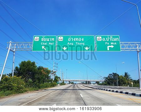 ANGTHONG THAILAND - NOVEMBER 27 : directional traffic sign on highway with clear blue sky on November 27 2016 in Angthong Thailand