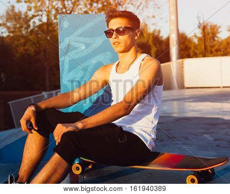 A skateboarder wearing white shirt, shorts is sitting on a skateboard in a skate-park on a sunset. Street foto with flare light of a young man on an urban background.