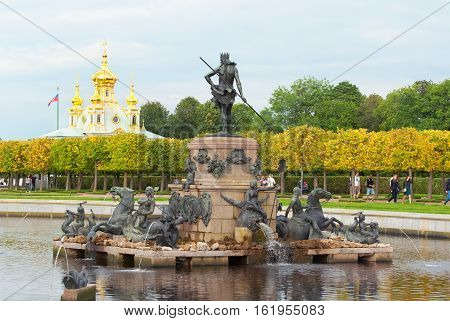 PETERHOF, SAINT - PETERSBURG, RUSSIA - AUGUST 19, 2016: The Upper Garden. The Neptune Fountain. On the background is The Grand Palace Church of Saints Peter and Paul