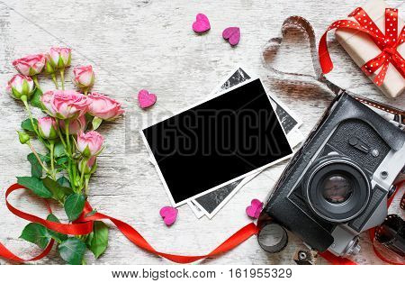 retro camera with blank photo pink roses wooden hearts and gift box over white wooden desk. valentines day background. top view