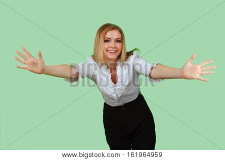 Pretty young woman with her hands wide apart on the green screen