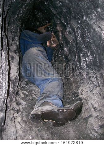Miner extracting from some coal by means of a pickaxe in a narrow gallery