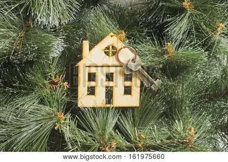 Model House and Key on Background of Christmass Tree - Christmas Wishes Concept