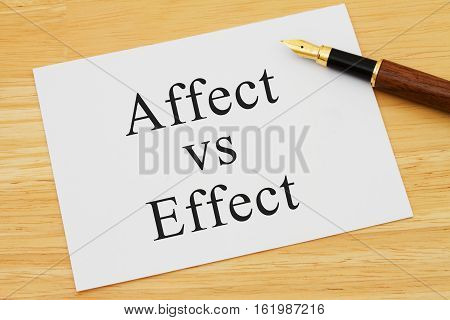 Learning to use proper grammar A white card on a desk with a pen with words Affect vs Effect