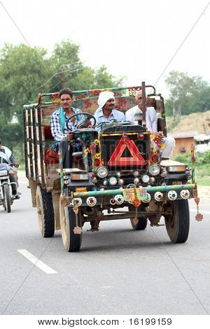 crazy road scene in India - small open car with people and goods