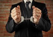 Man in handcuffs on brick wall background poster