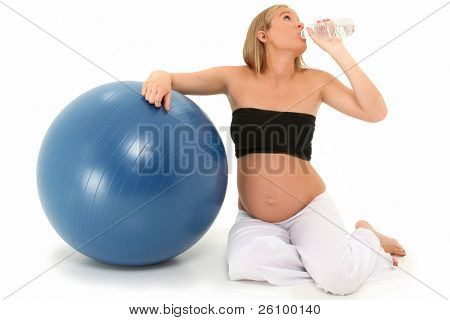 Beautiful 19 year old pregnant mother-to-be after workout drinking water over white background.