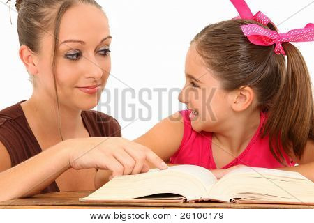 Beautiful 27 year old american teacher helping 7 year old student at desk over white background.