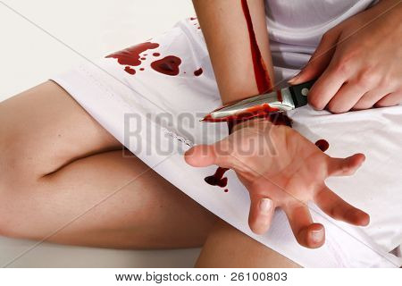 Woman in white cutting self with knife. Self injury.  Cutter.