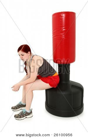 Attractive 19 year old woman sitting resting on free standing heavy bag after workout.