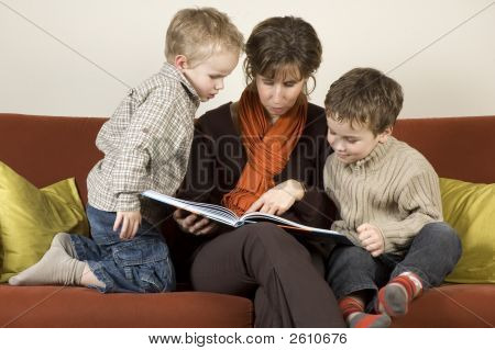 Mother And Two Sons Reading A Book 1