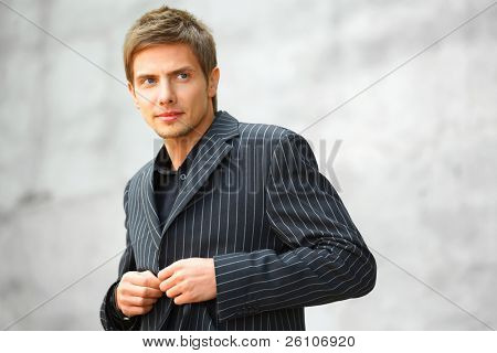 Closeup portrait shot of handsome young businessman, that clasps his suit. Outdoor.