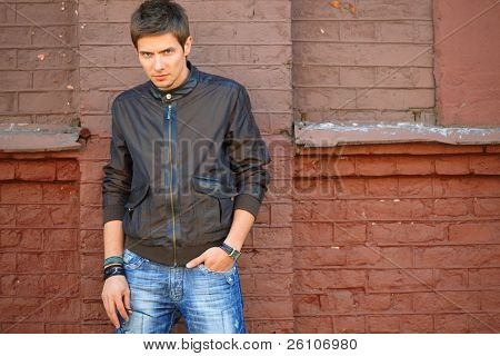 Fashion portrait shot of a young handsome man in jacket that stays near the brick wall.