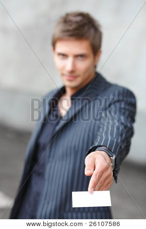 Portrait shot of smiling young businessman showing blank business card. Focus on card. Outdoor.
