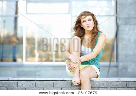 Cute student teenage girl sitting at urban scene. She is dreaming about something.