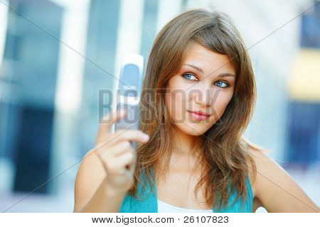 Smiling cute student teenage girl looking at mobile phone. Urban scene, closeup.