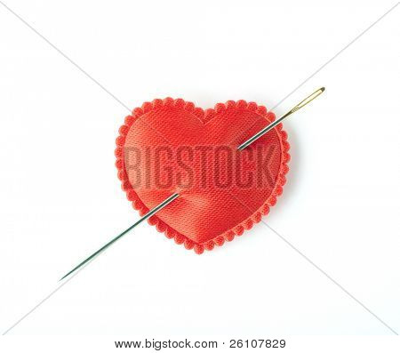 Red satin heart pierced with a sewing needle. Isolated on white. Closeup.