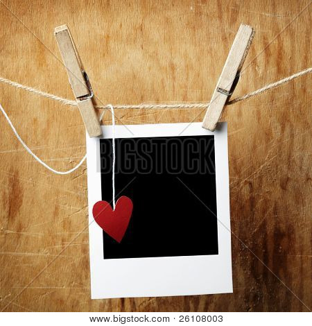 Blank instant photo and small red paper heart hanging on the clothesline. On dark grunge background.
