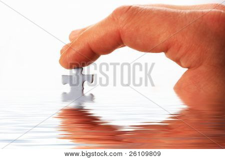 finger and puzzle in water on white