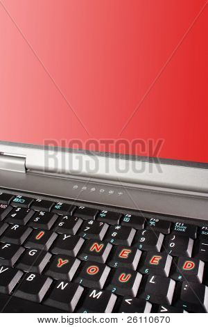 laptop black keyboard with words I need you and red screen copyspace