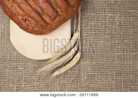 Fresh Loaf Of Bread With Ears Of Rye On The Breadboard Background