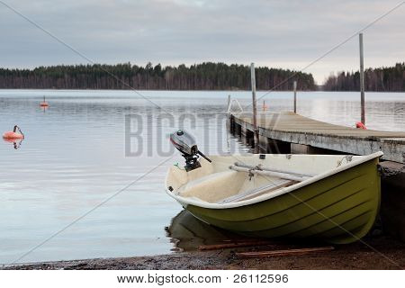 The Boat Is On The Shore Of The Lake.