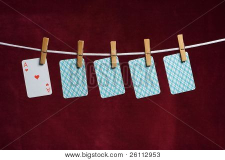 heart ace and four cards with clothes peg rope on red background