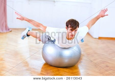 Healthy Man Making Exercises On Fitness Ball