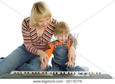 mother teach  baby play piano over white background