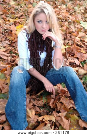 attractive young woman sitting on fallen leaves