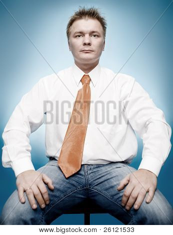 young businessman in white shirt and orange tie on blue background